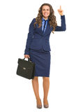 Smiling business woman with briefcase pointing up on copy space Stock Photography