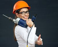 Smiling business woman builder holding drill tool on shoulder. Stock Photos