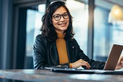 Smiling business woman in casuals at office stock images
