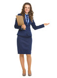 Smiling business woman with clipboard pointing on copy space Royalty Free Stock Image