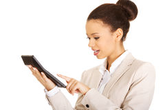 Smiling business woman counting on calculator. Royalty Free Stock Photography
