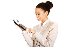 Smiling business woman counting on calculator. Royalty Free Stock Images