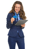 Smiling business woman with credit card using tablet pc Stock Photo