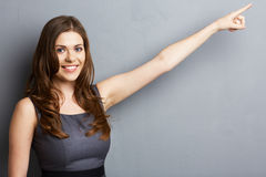 Smiling business woman finger pointing at the side. Royalty Free Stock Image
