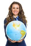 Smiling business woman giving earth globe Royalty Free Stock Photo