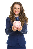 Smiling business woman giving piggy bank Royalty Free Stock Photos