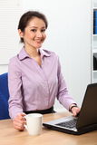 Smiling business woman having coffee at her desk Royalty Free Stock Image