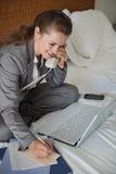 Smiling business woman having working phone calls. On bed in hotel room royalty free stock photos