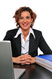 Smiling Business Woman at Her Desk. In front of her computer and a binder full of documents Royalty Free Stock Photography