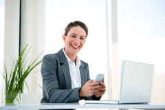 Smiling business woman on her mobile phone. Smiling business woman, at her desk, on her mobile phone Stock Photo