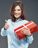 Smiling business woman hold red gift box show thumb up. Studio isolated Royalty Free Stock Photos