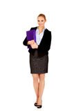 Smiling business woman holding a binder Stock Photography