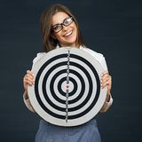 Smiling business woman holding black white target. Black background Stock Images