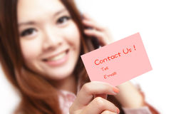 Smiling business woman holding a card (Contact Us) Stock Photo