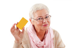 Smiling business woman holding credit card. Close-up portrait of mature smiling business woman holding credit card isolated on white background Stock Image