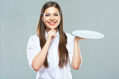 Smiling Business woman holding emty white plate. Studio isolated portrait of young business woman royalty free stock images