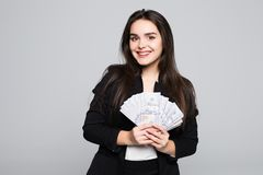 Smiling business woman holding money over gray background. Smiling business woman holding money over gray Royalty Free Stock Images