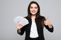 Smiling business woman holding money with thumbs up over gray background. Smiling business woman holding money over gray background Royalty Free Stock Photo