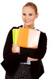 Smiling business woman holding notebooks Stock Photo