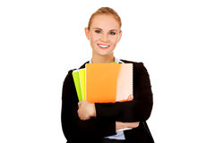 Smiling business woman holding notebooks Royalty Free Stock Image