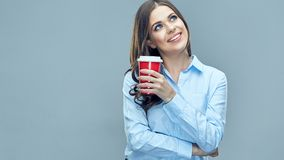 Smiling business woman holding red coffee glass looking to side. Break at work. Studio isolated Stock Photos