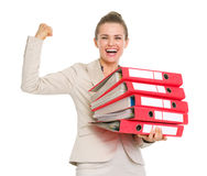 Smiling business woman holding stack of folders. And showing biceps Royalty Free Stock Photo
