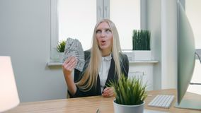 Smiling business woman holding wad of cash. Beautiful happy blond female sitting in office at workplace with computer stock footage