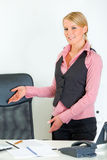 Smiling business woman inviting to sit on chair. Smiling modern business woman standing near office desk and inviting to sit on chair Stock Images