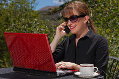 Smiling business woman on laptop and cell phone. Business woman with sunglasses on sitting at an outdoor table with her laptop and cell phone smiling Royalty Free Stock Images