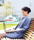 Smiling business woman with laptop in city Royalty Free Stock Photo
