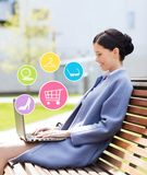 Smiling business woman with laptop in city. Business, technology, online shopping and people concept - young smiling woman with laptop computer and internet Stock Images