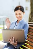 Smiling business woman with laptop in city Royalty Free Stock Photos