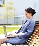 Smiling business woman with laptop in city Royalty Free Stock Photography