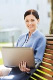 Smiling business woman with laptop in city Stock Photography