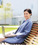 Smiling business woman with laptop in city Stock Photo