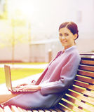 Smiling business woman with laptop in city. Business, technology and people concept - young smiling woman with laptop computer sitting on bench in city Stock Images