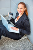 Smiling business woman with laptop and cup Stock Photography