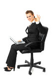 Smiling business woman with laptop showing ok Stock Images