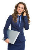 Smiling business woman with laptop talking cell phone Royalty Free Stock Images