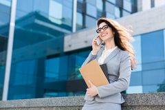 Portrait of business woman lawyer outdoor. Smiling business woman lawyer talking on the phone outdoor royalty free stock photo