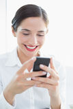 Smiling business woman looking at mobile phone Royalty Free Stock Photography