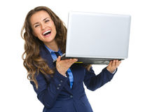 Smiling business woman looking out from laptop Stock Photo