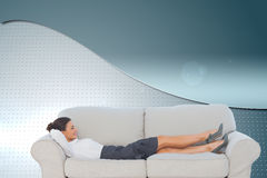 Smiling business woman lying down on the couch Royalty Free Stock Photo