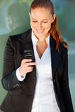 Smiling business woman near office building. Smiling modern business woman near office building looking on mobile Royalty Free Stock Image