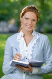 Smiling business woman with notebook in the garden Stock Image