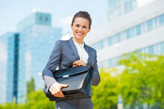 Smiling business woman in office district holding briefcase Stock Photo