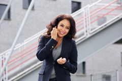 Smiling business woman outside on cellphone Royalty Free Stock Image