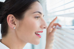 Smiling business woman peeking through blinds at office Royalty Free Stock Photo