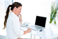 Smiling business woman on the phone. Smiling business woman, at her desk, on the phone Royalty Free Stock Photo