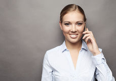 Smiling business woman phone talking,  on grey backgroun Royalty Free Stock Photo